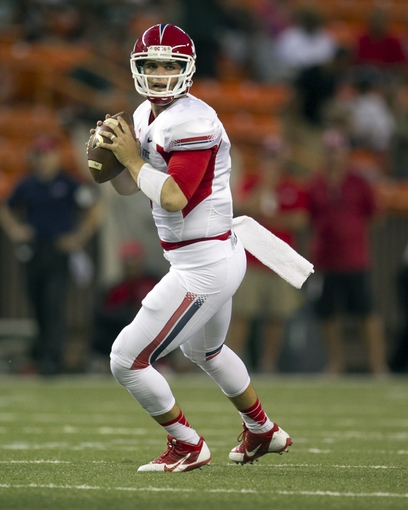 Sep 28, 2013; Honolulu, HI, USA; Fresno State quarterback Derek Carr (4) looks for an open receiver against Hawaii during the first quarter of the NCAA college football game at Aloha Stadium. Mandatory Credit: Marco Garcia-USA TODAY Sports