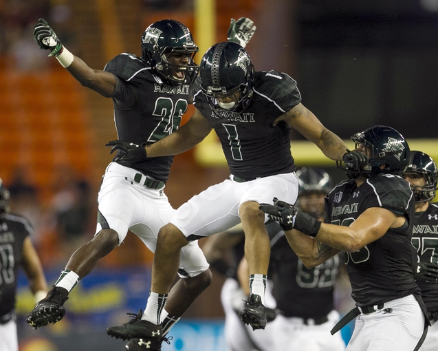 Sep 28, 2013; Honolulu, HI, USA; Hawaii defensive back Ne'Quan Phillips (1), center, celebrates with teammates Kwamane Bowens (26), left, and Brenden Daley (56) after Phillips made an interception against Fresno State in the fourth quarter of the NCAA college football game at Aloha Stadium. Mandatory Credit: Marco Garcia-USA TODAY Sports