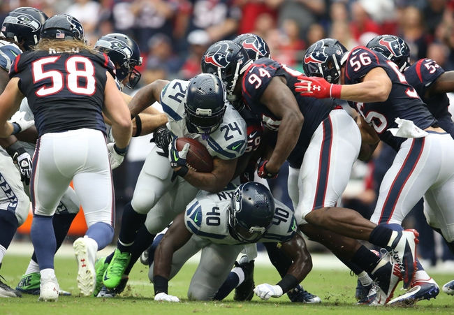Sep 29, 2013; Houston, TX, USA; Seattle Seahawks running back Marshawn Lynch (24) runs with the ball against Houston Texans defensive end Antonio Smith (94) in the first quarter at Reliant Stadium. Mandatory Credit: Matthew Emmons-USA TODAY Sports