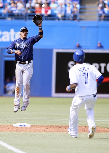 Sep 29, 2013; Toronto, Ontario, CAN; Tampa Bay Rays shortstop Yunel Escobar (11) catches a ball thrown by first baseman James Loney (not pictured) to start a run down of Toronto Blue Jays shortstop Jose Reyes (7) during the first inning at Rogers Centre. Mandatory Credit: John E. Sokolowski-USA TODAY Sports