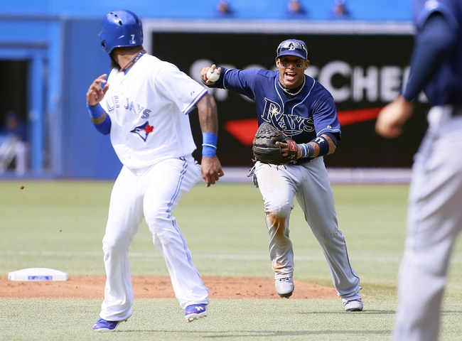 Sep 29, 2013; Toronto, Ontario, CAN; Tampa Bay Rays shortstop Yunel Escobar (11) goes to tag Toronto Blue Jays shortstop Jose Reyes (7) during a run down in the first inning at Rogers Centre. Mandatory Credit: John E. Sokolowski-USA TODAY Sports