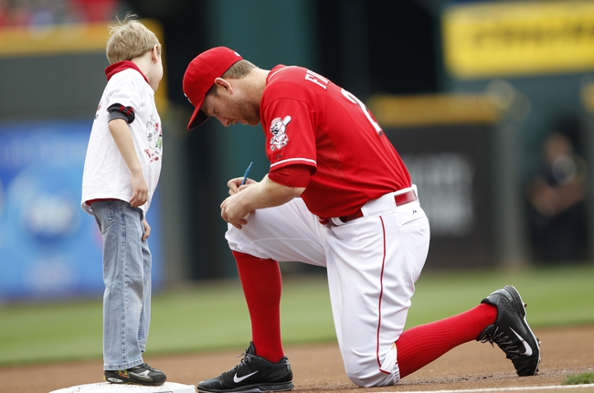 Sep 29, 2013; Cincinnati, OH, USA; Cincinnati Reds third baseman Todd Frazier (21) signs an autograph for a young fan prior to the game against the Pittsburgh Pirates at Great American Ball Park. Mandatory Credit: Frank Victores-USA TODAY Sports