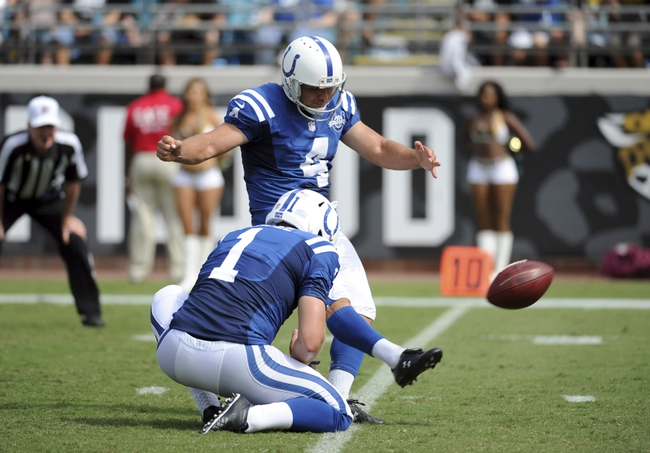 Sep 29, 2013; Jacksonville, FL, USA; Indianapolis Colts kicker Adam Vinatieri (4) kicks an extra point as punter Pat McAfee (1) holds during the second half of the game against the Jacksonville Jaguars at EverBank Field. Mandatory Credit: Melina Vastola-USA TODAY Sports