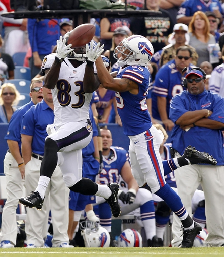 Sep 29, 2013; Orchard Park, NY, USA; Baltimore Ravens wide receiver Deonte Thompson (83) catches a pass as Buffalo Bills defensive back Brandon Burton (29) defends during the second half at Ralph Wilson Stadium. Bills beat the Ravens 23-20. Mandatory Credit: Kevin Hoffman-USA TODAY Sports