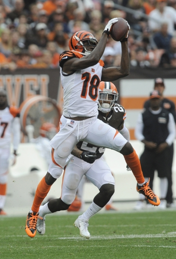 Sep 29, 2013; Cleveland, OH, USA; Cincinnati Bengals wide receiver A.J. Green (18) makes a catch as Cleveland Browns cornerback Joe Haden (23) defends during the fourth quarter at FirstEnergy Stadium. The Browns beat the Bengals 17-6.  Mandatory Credit: Ken Blaze-USA TODAY Sports