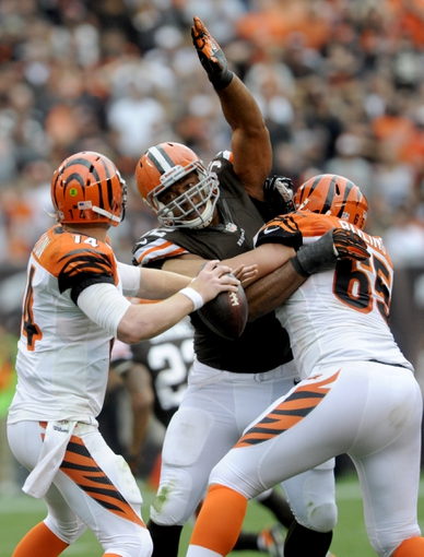 Sep 29, 2013; Cleveland, OH, USA; Cleveland Browns defensive end Desmond Bryant (92) tries to break through the block of Cincinnati Bengals guard Clint Boling (65) to get to Cincinnati Bengals quarterback Andy Dalton (14) during the fourth quarter at FirstEnergy Stadium. The Browns beat the Bengals 17-6.  Mandatory Credit: Ken Blaze-USA TODAY Sports