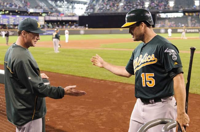 Sep 29, 2013; Seattle, WA, USA; Oakland Athletics manager Bob Melvin (6) and Oakland Athletics left fielder Seth Smith (15) high five after Smith scored a run against the Seattle Mariners off a RBI double hit by Oakland Athletics designated hitter Brandon Moss (not pictured) during the second inning at Safeco Field. Mandatory Credit: Steven Bisig-USA TODAY Sports