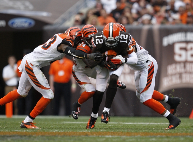 Sep 29, 2013; Cleveland, OH, USA; Cleveland Browns wide receiver Josh Gordon (12) gets tackled by a gang of Cincinnati Bengals during the fourth quarter at FirstEnergy Stadium. Browns beat the Bengals 17-6. Mandatory Credit: Raj Mehta-USA TODAY Sports