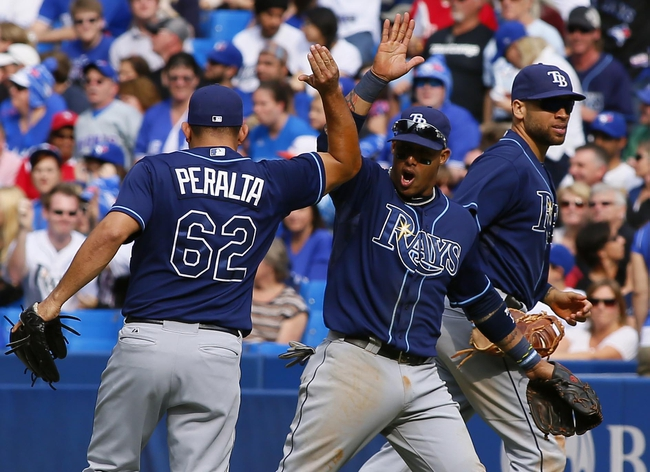 Sep 29, 2013; Toronto, Ontario, CAN; Tampa Bay Rays shortstop Yunel Escobar (11) celebrates a double play against the Toronto Blue Jays with  Rays pitcher Joel Peralta (62) in the seventh inning at Rogers Centre. Tampa defeated Toronto 7-6. Mandatory Credit: John E. Sokolowski-USA TODAY Sports