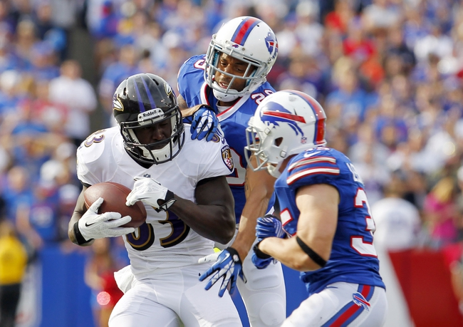Sep 29, 2013; Orchard Park, NY, USA; Buffalo Bills defensive back Brandon Burton (29) and defensive back Jim Leonhard (35) look to make a tackle on Baltimore Ravens wide receiver Deonte Thompson (83) after a catch during the second half at Ralph Wilson Stadium. Bills beat Ravens 23 to 20.  Mandatory Credit: Timothy T. Ludwig-USA TODAY Sports