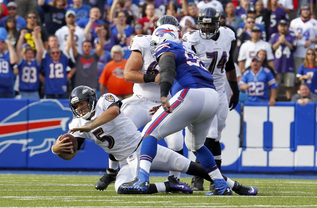 Sep 29, 2013; Orchard Park, NY, USA; Buffalo Bills defensive tackle Marcell Dareus (99) knocks down Baltimore Ravens quarterback Joe Flacco (5) during the second half at Ralph Wilson Stadium. Bills beat Ravens 23 to 20.  Mandatory Credit: Timothy T. Ludwig-USA TODAY Sports