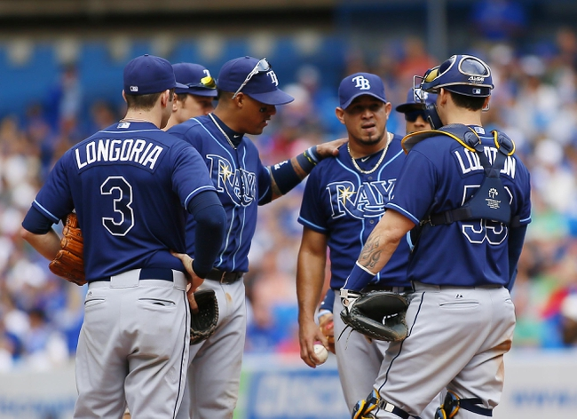 Sep 29, 2013; Toronto, Ontario, CAN; Tampa Bay Rays shortstop Yunel Escobar (11) and third baseman Evan Longoria (3) and catcher Jose Lobaton (59) talk to pitcher Joel Peralta (center) in the eighth inning against the Toronto Blue Jays at Rogers Centre. Tampa defeated Toronto 7-6. Mandatory Credit: John E. Sokolowski-USA TODAY Sports