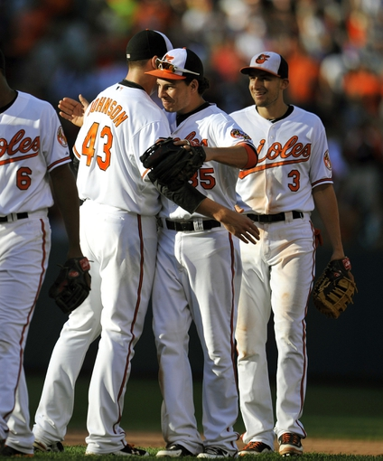 Sep 29, 2013; Baltimore, MD, USA; Baltimore Orioles teammates Jim Johnson (43) and Danny Valencia (35) celebrate after the game against the Boston Red Sox at at Oriole Park at Camden Yards. The Orioles won 7-6. Mandatory Credit: Joy R. Absalon-USA TODAY Sports