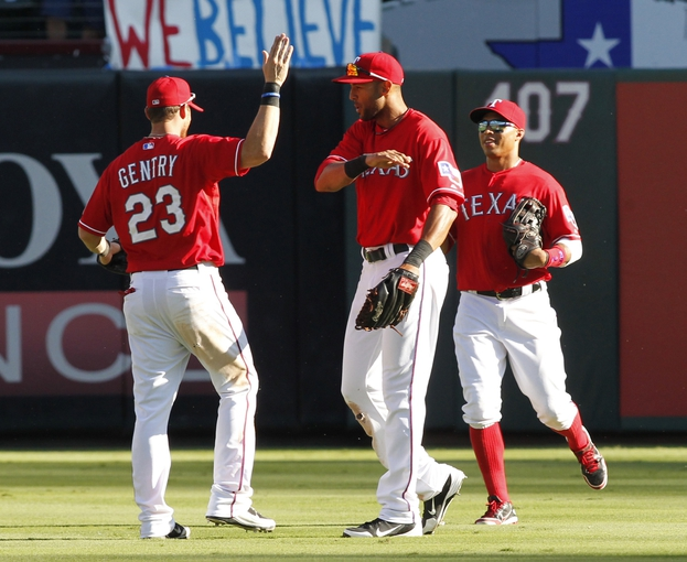 Sep 29, 2013; Arlington, TX, USA;Texas Rangers left fielder Craig Gentry (23) right fielder Alex Rios (51) and center fielder Leonys Martin (2) celebrate after the game against the Los Angeles Angels at Rangers Ballpark in Arlington. The Rangers beat the Angels 6-2.  Mandatory Credit: Tim Heitman-USA TODAY Sports