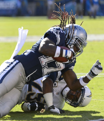 Sep 29, 2013; San Diego, CA, USA; Dallas Cowboys wide receiver Dwayne Harris (17) is tackled by San Diego Chargers defensive back Darrell Stuckey (25) on a second half kickoff return at Qualcomm Stadium.  Mandatory Credit: Robert Hanashiro-USA TODAY Sports
