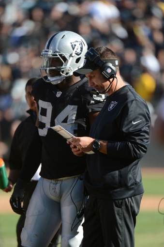Sep 29, 2013; Oakland, CA, USA; Oakland Raiders head coach Dennis Allen (right) and outside linebacker Kevin Burnett (94) looks on against the Washington Redskins during the fourth quarter at O.co Coliseum. The Redskins defeated the Raiders 24-14. Mandatory Credit: Kyle Terada-USA TODAY Sports