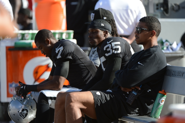 Sep 29, 2013; Oakland, CA, USA; Oakland Raiders quarterback Terrelle Pryor (2, far right) sits on the bench with punter Marquette King (7) and defensive back Chimdi Chekwa (35) during the fourth quarter at O.co Coliseum. The Redskins defeated the Raiders 24-14. Mandatory Credit: Kyle Terada-USA TODAY Sports
