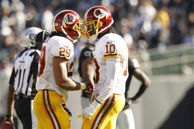 Sep 29, 2013; Oakland, CA, USA; Washington Redskins quarterback Robert Griffin III (10) talks with running back Roy Helu (29) after Helu picked up a first down against the Oakland Raiders late in the fourth quarter at O.co Coliseum. The Redskins defeated the Raiders 24-14. Mandatory Credit: Cary Edmondson-USA TODAY Sports