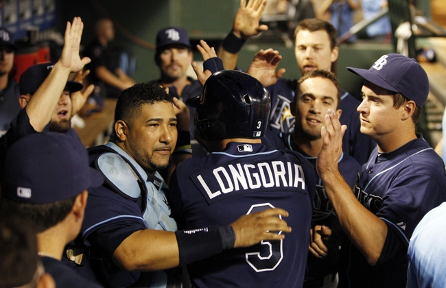 Sep 30, 2013; Arlington, TX, USA; Tampa Bay Rays third baseman Evan Longoria (3) is welcomed back to the dugout after scoring a run against the Texas Rangers during the sixth inning at Rangers Ballpark at Arlington. Mandatory Credit: Tim Heitman-USA TODAY Sports