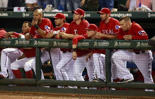 Sep 30, 2013; Arlington, TX, USA; Members of the Texas Rangers look out from the dugout in the 9th inning of the game against the Tampa Bay Rays at Rangers Ballpark at Arlington. Mandatory Credit: Tim Heitman-USA TODAY Sports