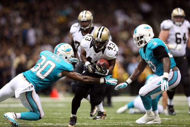 Sep 30, 2013; New Orleans, LA, USA; New Orleans Saints running back Darren Sproles (43) carries the ball between Miami Dolphins strong safety Chris Clemons (30) and middle linebacker Dannell Ellerbe (59) in the second half at Mercedes-Benz Superdome. New Orleans defeated Miami 38-17. Mandatory Credit: Crystal LoGiudice-USA TODAY Sports