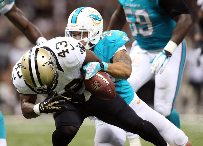 Sep 30, 2013; New Orleans, LA, USA;  Miami Dolphins safety Jimmy Wilson (27) causes New Orleans Saints running back Darren Sproles (43) to fumble in the fourth quarter at Mercedes-Benz Superdome. New Orleans defeated Miami 38-17. Mandatory Credit: Crystal LoGiudice-USA TODAY Sports