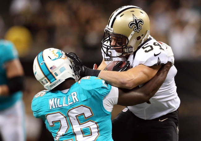 Sep 30, 2013; New Orleans, LA, USA; New Orleans Saints outside linebacker Will Herring (54) is taken down by Miami Dolphins running back Lamar Miller (26) as he carries the ball after an interception in the fourth quarter at Mercedes-Benz Superdome. New Orleans defeated Miami 38-17. Mandatory Credit: Crystal LoGiudice-USA TODAY Sports