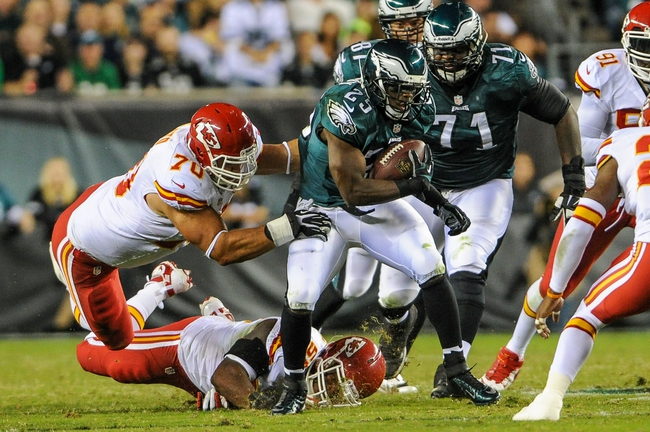 Sep 19, 2013; Philadelphia, PA, USA; Kansas City Chiefs inside linebacker Akeem Jordan (55) and defensive end Mike DeVito (70) tackle Philadelphia Eagles running back LeSean McCoy (25) during the second quarter of the game at Lincoln Financial Field. Mandatory Credit: John Geliebter-USA TODAY