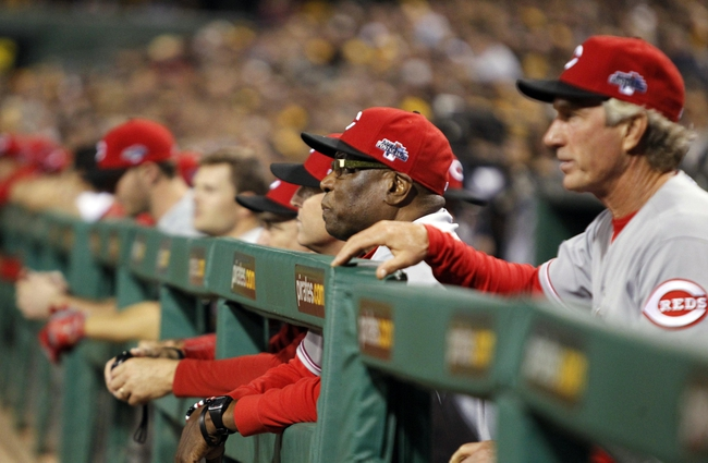 Oct 1, 2013; Pittsburgh, PA, USA; Cincinnati Reds coaches including manager Dusty Baker (middle) in the dugout in the fourth inning of the National League wild card playoff baseball game against the Pittsburgh Pirates at PNC Park. Mandatory Credit: Charles LeClaire-USA TODAY Sports