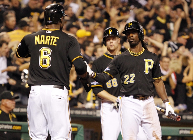 Oct 1, 2013; Pittsburgh, PA, USA; Pittsburgh Pirates left fielder Starling Marte (6) is welcomed back to the dugout by center fielder Andrew McCutchen (22) after scoring a run against the Cincinnati Reds in the fourth inning of the National League wild card playoff baseball game at PNC Park. Mandatory Credit: Charles LeClaire-USA TODAY Sports