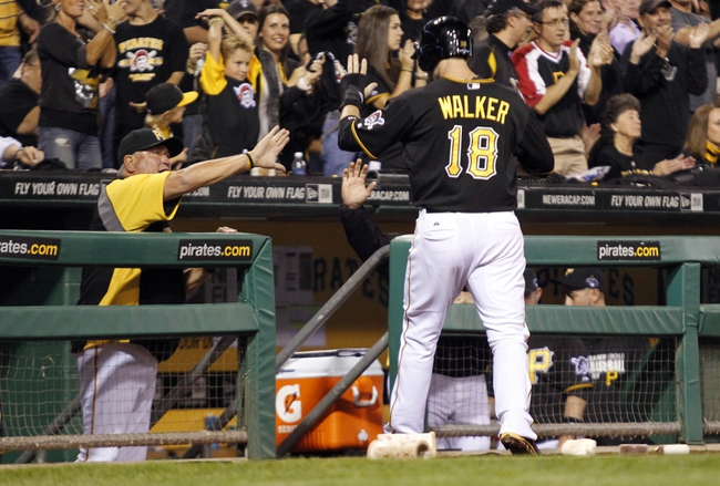 Oct 1, 2013; Pittsburgh, PA, USA; Pittsburgh Pirates second baseman Neil Walker (18) is welcomed back to the dugout by manager Clint Hurdle (left) after scoring a run in the fourth inning of the National League wild card playoff baseball game against the Cincinnati Reds at PNC Park. Mandatory Credit: Charles LeClaire-USA TODAY Sports