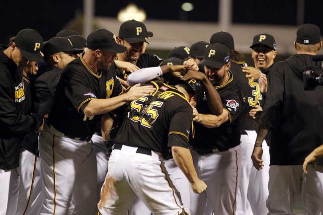 Oct 1, 2013; Pittsburgh, PA, USA; Pittsburgh Pirates catcher Russell Martin (55) is mobbed in celebration by his teammates after defeating the Cincinnati Reds in the National League wild card playoff baseball game at PNC Park. The Pirates won 6-2. Mandatory Credit: Charles LeClaire-USA TODAY Sports
