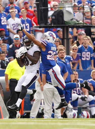 Sep 29, 2013; Orchard Park, NY, USA; Baltimore Ravens wide receiver Deonte Thompson (83) makes a catch as Buffalo Bills defensive back Brandon Burton (29) defends at Ralph Wilson Stadium. Bills beat the Ravens 23-20. Mandatory Credit: Kevin Hoffman-USA TODAY Sports