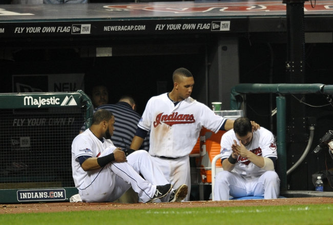 Oct 2, 2013; Cleveland, OH, USA; Cleveland Indians designated hitter Carlos Santana (left), left fielder Michael Brantley (center) and second baseman Jason Kipnis react after losing to the Tampa Bay Rays in the American League wild card playoff game at Progressive Field. Tampa Bay won 4-0. Mandatory Credit: David Richard-USA TODAY Sports