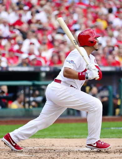 Oct 3, 2013; St. Louis, MO, USA; St. Louis Cardinals center fielder Jon Jay hits a single against the Pittsburgh Pirates in the second inning in game one of the National League divisional series playoff baseball game at Busch Stadium. Mandatory Credit: Scott Rovak-USA TODAY Sports