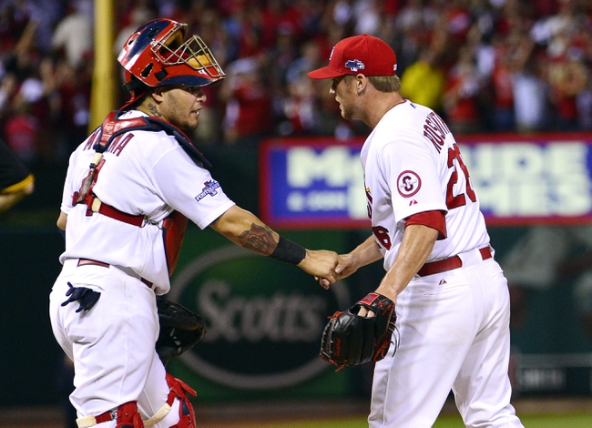 Oct 3, 2013; St. Louis, MO, USA; St. Louis Cardinals catcher Yadier Molina (4) and relief pitcher Trevor Rosenthal (26) celebrate their victory over the Pittsburgh Pirates in game one of the National League divisional series playoff baseball game at Busch Stadium. Mandatory Credit: Scott Rovak-USA TODAY Sports