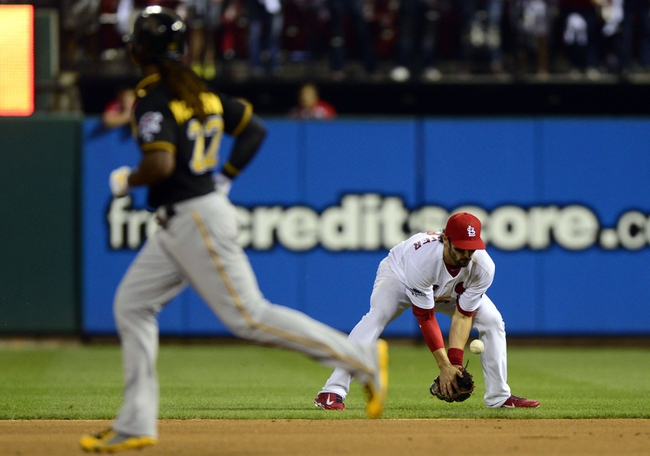 Oct 3, 2013; St. Louis, MO, USA; St. Louis Cardinals second baseman Matt Carpenter (13) bobbles a ground ball as Pittsburgh Pirates center fielder Andrew McCutchen (22) looks on during the ninth inning in game one of the National League divisional series playoff baseball game at Busch Stadium. St. Louis defeated Pittsburgh 9-1. Mandatory Credit: Jeff Curry-USA TODAY Sports
