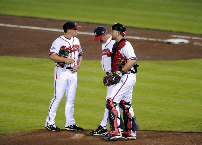 Oct 3, 2013; Atlanta, GA, USA; Atlanta Braves pitching coach Roger McDowell (center) talks with starting pitcher Kris Medlen (right) on the mound during the fourth inning against the Los Angeles Dodgers of game one of the National League divisional series playoff baseball game at Turner Field. Mandatory Credit: Dale Zanine-USA TODAY Sports