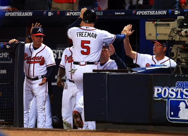 Oct 3, 2013; Atlanta, GA, USA; Atlanta Braves first baseman Freddie Freeman (5) celebrates with teammates after scoring against the Los Angeles Dodgers during the fourth inning of game one of the National League divisional series playoff baseball game at Turner Field. Mandatory Credit: Daniel Shirey-USA TODAY Sports