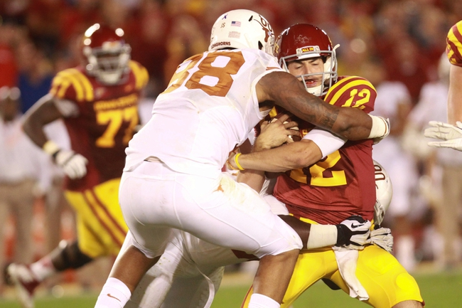 Oct 3, 2013; Ames, IA, USA; Iowa State Cyclones quarter back Sam Richardson (12) is sacked by Texas Longhorns defensive end Cedric Reed (88) during the second quarter at Jack Trice Stadium. Mandatory Credit: Reese Strickland-USA TODAY Sports