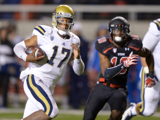 Oct 3, 2013; Salt Lake City, UT, USA; UCLA Bruins quarterback Brett Hundley (17) is pursued by Utah Utes defensive back Eric Rowe (18) on a 36-yard touchdown run in the fourth quarter at Rice-Eccles Stadium. UCLA defeated Utah 34-27. Mandatory Credit: Kirby Lee-USA TODAY Sports