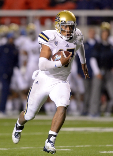 Oct 3, 2013; Salt Lake City, UT, USA; UCLA Bruins quarterback Brett Hundley (17) scores on a 36-yard touchdown run in the fourth quarter against the Utah Utes at Rice-Eccles Stadium. UCLA defeated Utah 34-27. Mandatory Credit: Kirby Lee-USA TODAY Sports