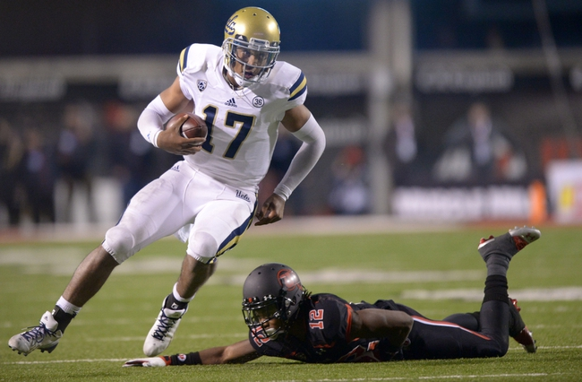 Oct 3, 2013; Salt Lake City, UT, USA; UCLA Bruins quarterback Brett Hundley (17) is pressured by Utah Utes defensive back Justin Thomas (12) at Rice-Eccles Stadium. UCLA defeated Utah 34-27. Mandatory Credit: Kirby Lee-USA TODAY Sports