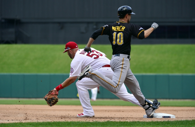 Oct 4, 2013; St. Louis, MO, USA; Pittsburgh Pirates batter Jordy Mercer (10) beats the throw to St. Louis Cardinals first baseman Matt Adams (53) for an infield single in the seventh inning in game two of the National League divisional series playoff baseball game at Busch Stadium. Mandatory Credit: Scott Rovak-USA TODAY Sports
