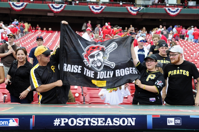 Oct 4, 2013; St. Louis, MO, USA; Fans of the Pittsburgh Pirates cheer and wave a flag after game two of the National League divisional series playoff baseball game against the St. Louis Cardinals at Busch Stadium. Mandatory Credit: Jeff Curry-USA TODAY Sports