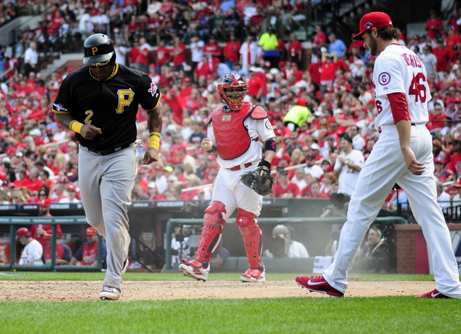 Oct 4, 2013; St. Louis, MO, USA; Pittsburgh Pirates right fielder Marlon Byrd (2) scores on a sacrifice fly by catcher Russell Martin (not pictured) as St. Louis Cardinals catcher Yadier Molina (4) and relief pitcher Kevin Siegrist (46) looks on during the seventh inning in game two of the National League divisional series playoff baseball game at Busch Stadium. Pittsburgh defeated St. Louis 7-1. Mandatory Credit: Jeff Curry-USA TODAY Sports