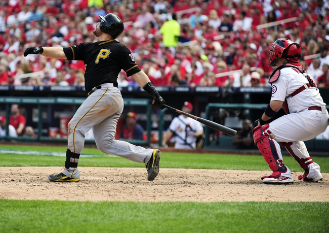Oct 4, 2013; St. Louis, MO, USA; Pittsburgh Pirates catcher Russell Martin (55) hits a one run sacrifice fly off of St. Louis Cardinals relief pitcher Kevin Siegrist (not pictured) during the seventh inning in game two of the National League divisional series playoff baseball game at Busch Stadium. Pittsburgh defeated St. Louis 7-1. Mandatory Credit: Jeff Curry-USA TODAY Sports