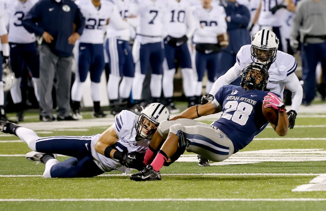 Oct 4, 2013; Logan, UT, USA; Utah State Aggies running back Joey DeMartino (28) is tackled by Brigham Young Cougars offensive linesman Edward Fusi (50) in the second half at Romney Stadium.  BYU won 31-14. Mandatory Credit: Chris Nicoll-USA TODAY Sports