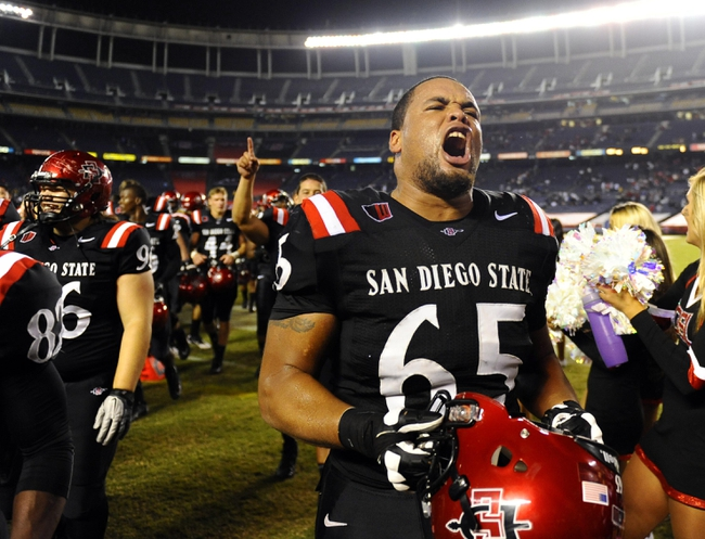 Oct 4, 2013; San Diego, CA, USA; San Diego State offensive lineman Japheth Gordon (65) celebrates following a 51-44 overtime win against the Nevada Wolf Pack at Qualcomm Stadium. Mandatory Credit: Christopher Hanewinckel-USA TODAY Sports