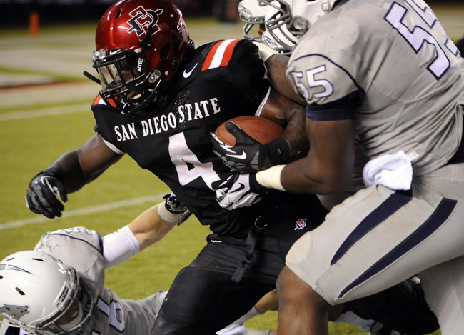 Oct 4, 2013; San Diego, CA, USA; San Diego State running back Adam Muema (4) battles for extra yards during the second half against the Nevada Wolf Pack at Qualcomm Stadium. Mandatory Credit: Christopher Hanewinckel-USA TODAY Sports